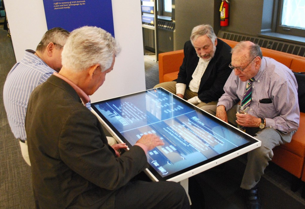 4 older men play a word game together on a touch table at the Word Play exhibit at the American Writers Museum in Chicago, IL