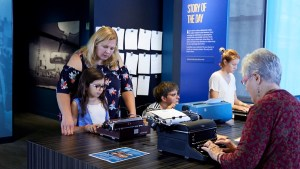 Adults and children interact with typewriters at the American Writers Museum