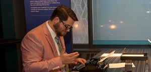 A man using a typewriter at the American Writers Museum