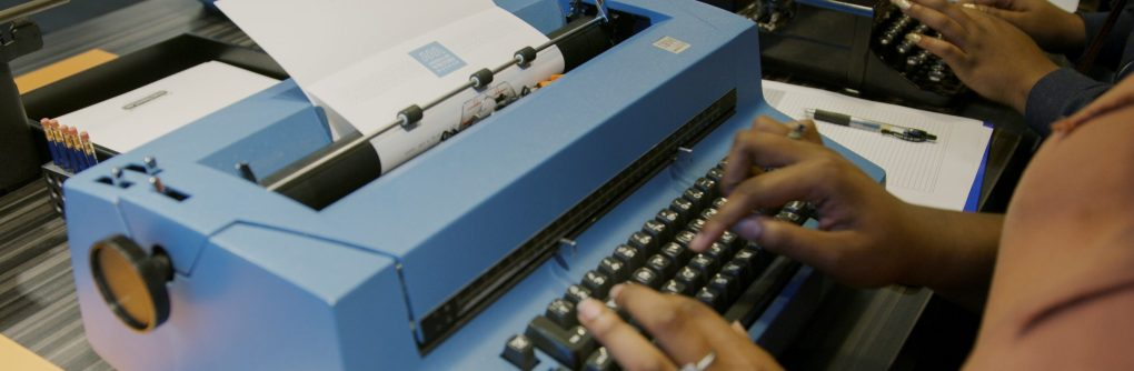 A visitor typing on a large blue IBM typewriter at the American Writers Museum in Chicago, IL