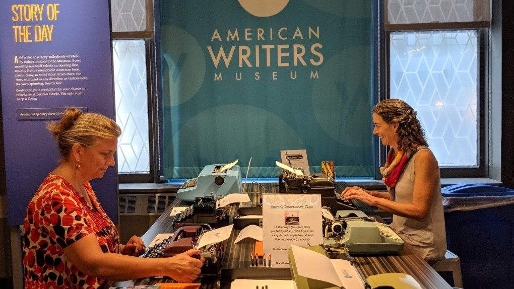 Two women typing at typewriters at the Story of the Day exhibit