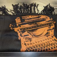 A black scarf with an orange silkscreen design of an Underwood typewriter on it.