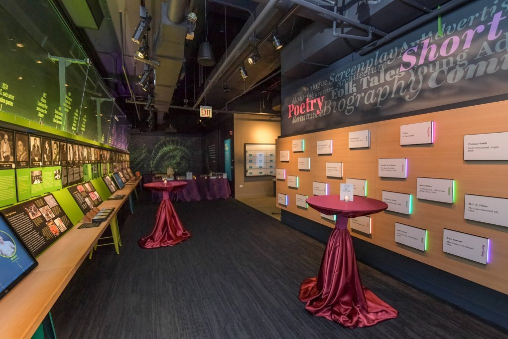 A cocktail event at the American Writers Museum in which 2 tables are set up in the Nation of Writers gallery