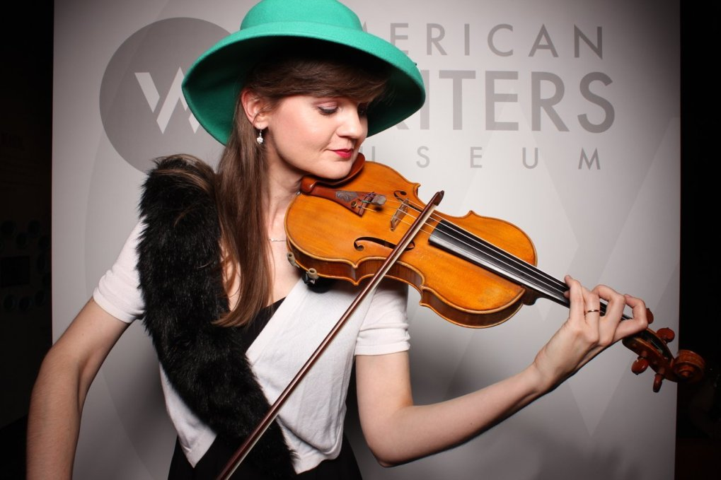 A woman wearing a teal hat playing the violin at the American Writers Museum