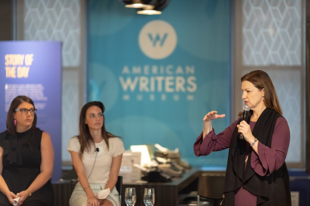 A woman with a microphone presenting at the American Writers Museum