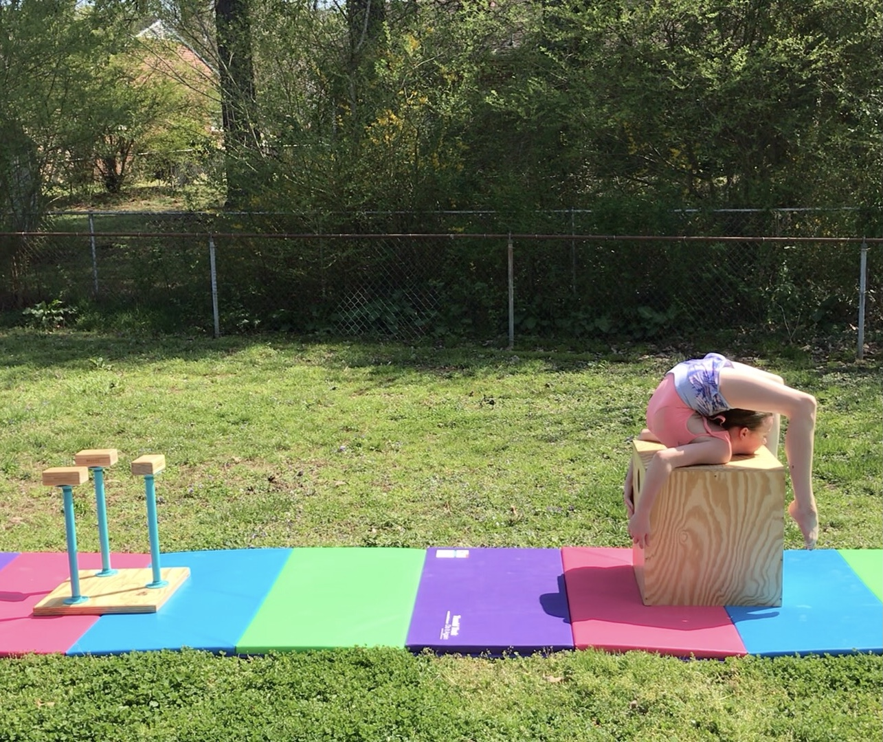 Jocelyn performs a backbend on a cube that is part of her outdoor stage