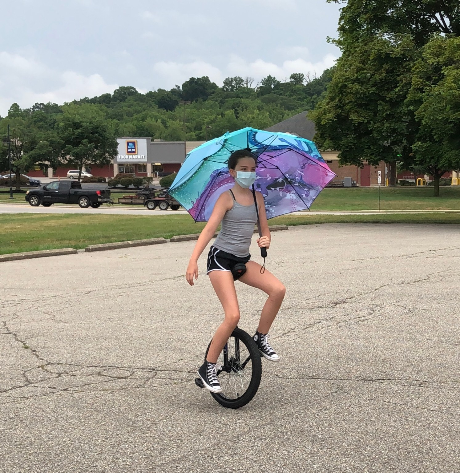 my nose turns red youth circus performer unicycling with an umbrella while wearing a mask