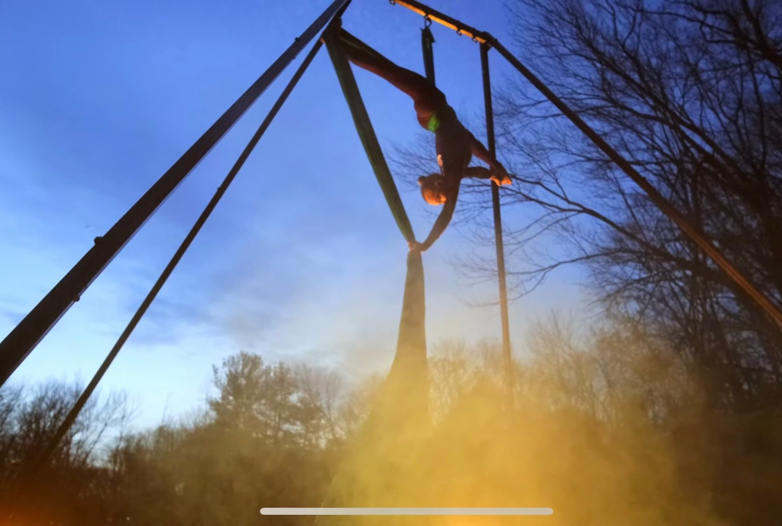 Aerialist performs she splits upside down on an aerial fabric
