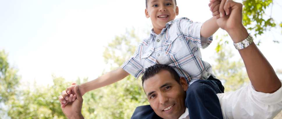 Hispanic Father And Son Having Fun In The Park
