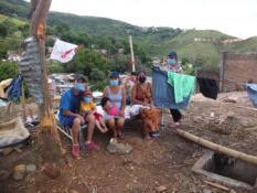 Eine Familie sitzt vor ihrer zerstörten Hütte in Siloé