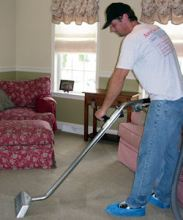 Worker steam-cleaning a living room carpet.