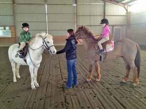 Photo of two young girls being shown how to ride ponies