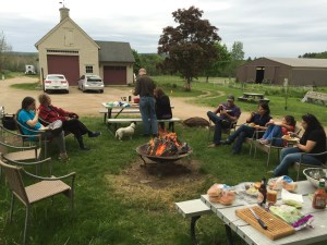 Photo of group of people sitting around an outdoor fire eating food