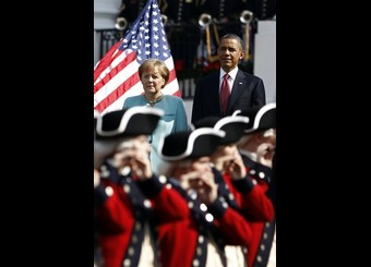 U.S. President Obama and German Chancellor Merkel watch Old Guard Fife and Drum Corps parade past during arrival ceremony at White House