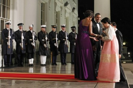 U.S. President Obama watches as his wife greets South Korean first lady as she and President Lee arrive for a state dinner in Washington