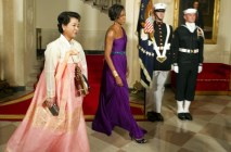 First Lady Michelle Obama (C) walks with