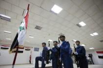 Members of Iraqi military salute raising of Iraq flag at a signing ceremony at Camp Adder near Nasiriyah