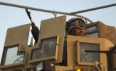 Specialist Rodriguez smiles as he mans gun of MRAP vehicle near the Kuwaiti border as part of the last U.S. military convoy to leave Iraq