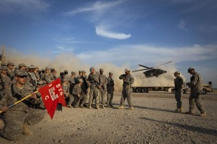 Soldiers from the 3rd Brigade Combat Team, 1st Cavalry Division hold their unit's flag for a photograph while waiting at a staging area in Camp Adder to be part of the last U.S. military convoy to leave the country near Nasiriyah, Iraq