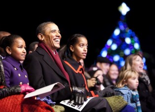 US President Obama and his daughters watch the lighting of the National Christmas Tree in Washington