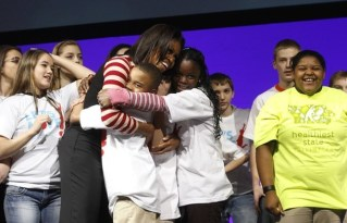 """U.S. First Lady Michelle Obama hugs children after they danced together to promote her """"Let's Move"""" initiative in Des Moines"""