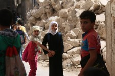 "On 21 September 2016 in eastern Aleppo in the Syrian Arab Republic, Judy (white head scarf), 9, and her schoolmates walk to school past the rubble of nearby houses.  ""I go to school every day, except for the times when I hear the planes,"" Judy explains.  ""I want the road to reopen so I can go see my brother who lives in another city and just got married. I haven't even met his wife yet,"" says Judy.  Instead, the road remained closed due to heavy bombardment and shelling. In Judy's neighborhood, electricity is largely unavailable as there is a fuel shortage.  One in four schools in Syria are not functioning and over two million children remain out of school, with another 400,000 at risk of dropping out."