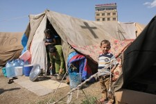 Family_in_refugee_camp_in_yard_of_St._Elia_Church_in_Erbil,_Iraq.1