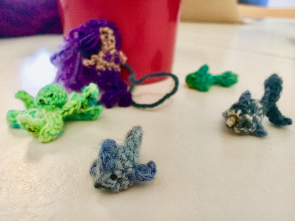 Crocheted sea creatures, including fish and a mermaid