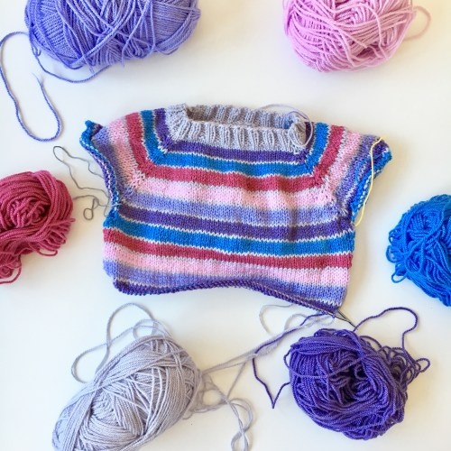 A colourful half-finished Raglan striped sweater, surrounded by balls of yarn.