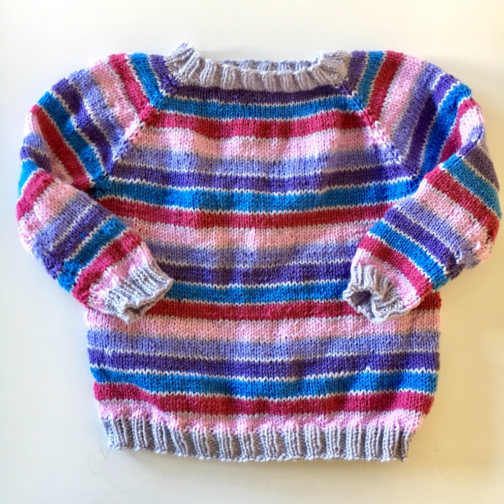 A striped child's sweater before wet blocking acrylic yarn - blocking makes a huge difference even to acrylics.