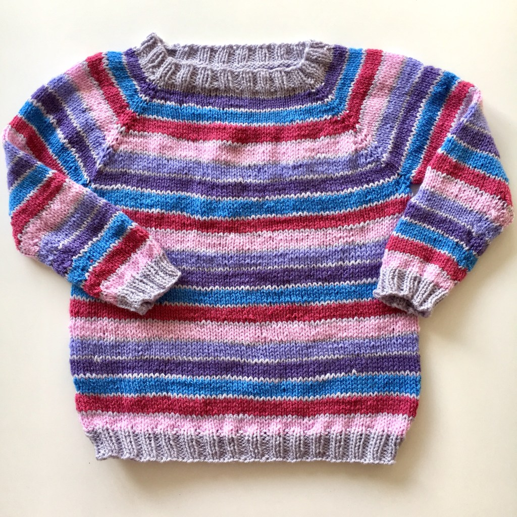 A striped child's sweater after wet blocking acrylic yarn - blocking makes a huge difference even to acrylics.