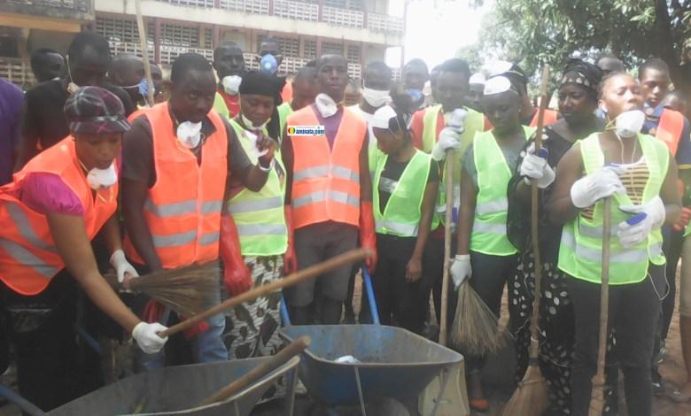 Des jeunes membres du Réseau des Organisations pour une Lutte Uniforme assainisse leur quartier Yimbaya