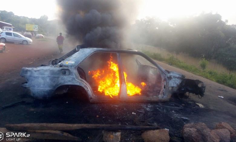 Une voiture brulée au beau milieu de la route lors d'une violente manifestation