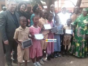Des cadres de la fondation Orange et Plan Guinée avec des écoliers munis des tablettes