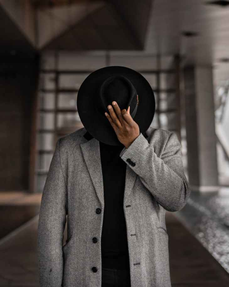 man covering his face with hat
