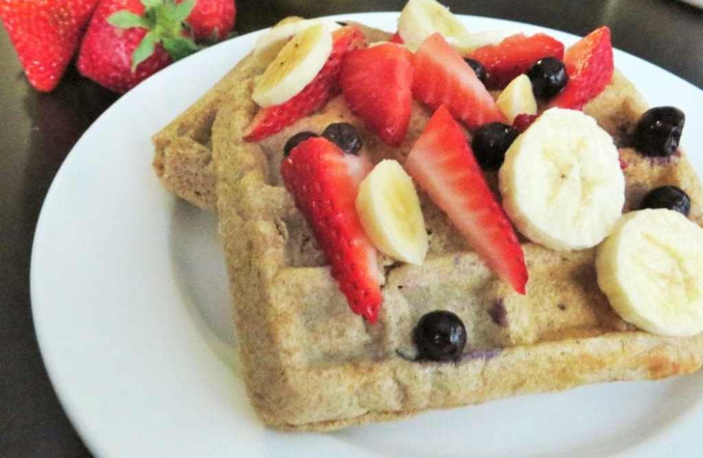 Whole wheat waffles topped with fresh fruit and a drizzle of maple syrup.