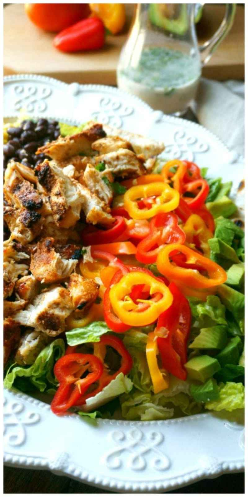 A southwestern spin on a classic cobb salad--crisp romaine is topped with corn, avocado, tomatoes, peppers, grilled chicken. Served with cheese quesadillas in place of croutons and completed with a Cilantro Lime Dressing.