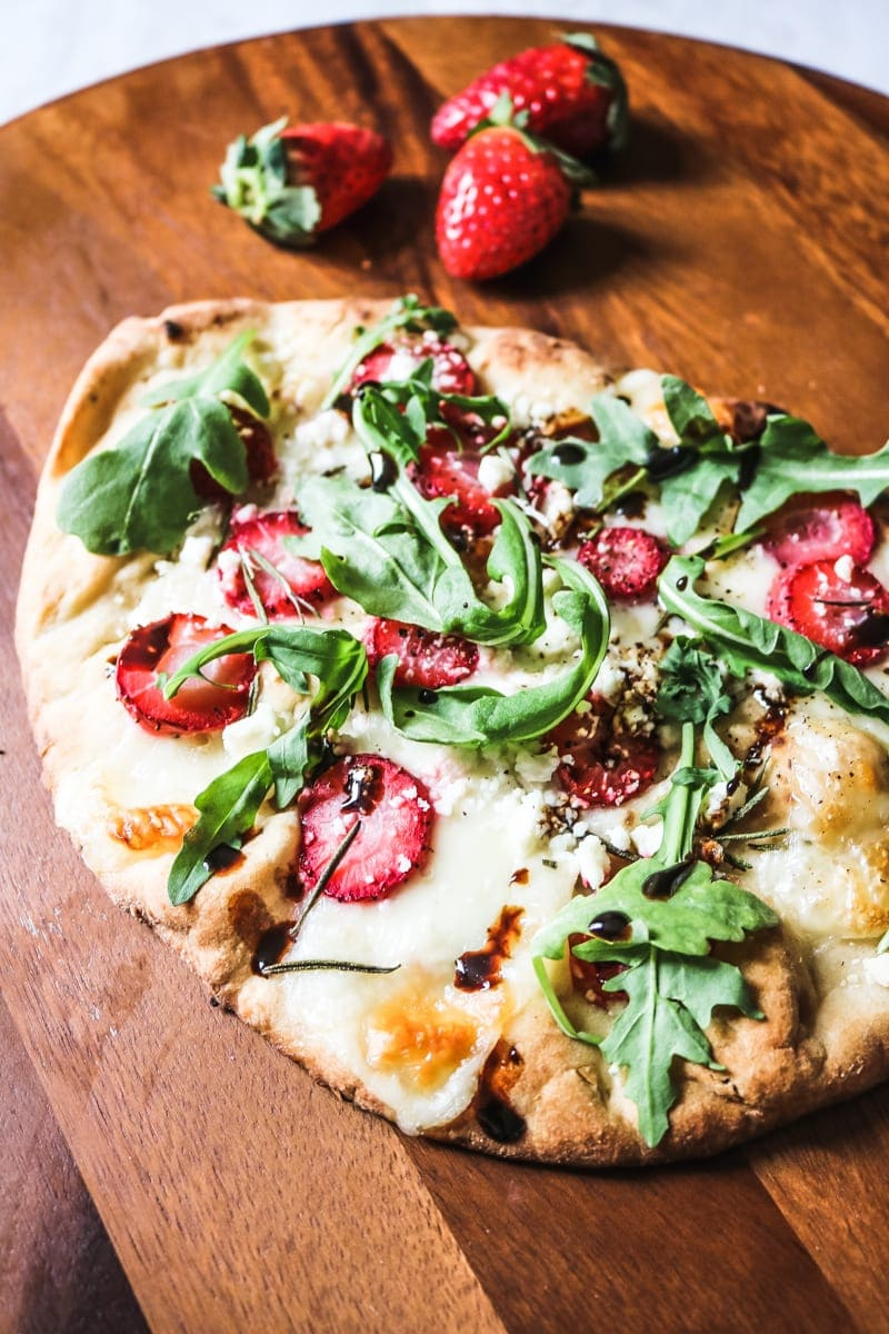Strawberry and Arugula Pizza: A cheese pizza is brought to life with subtle sweetness from strawberries, sharpness from arugula and a rich balsamic drizzle. It is a pizza like you have never had and will always remember!