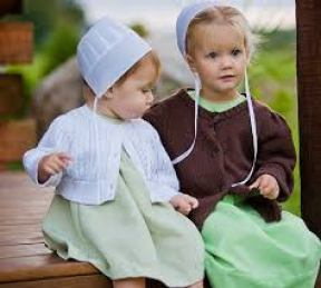 Two young Amish girls sitting on a porch.