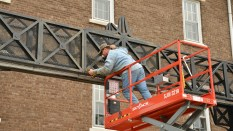 Conder screws the center aluminum panel onto the steel structure.