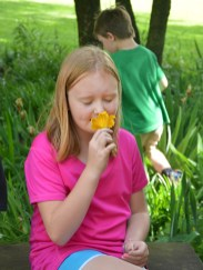 Samantha Foley enjoys the scent from a flower she picked while visiting Constitution Square Park Tuesday morning.