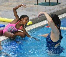 Photo by ROBIN HART/robin.hart@amnews.com Brianna Hylton follows Katie Lamb's instructions on how to use her arms when she get into the pool.