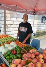 Terry Doneghy watches people pass by as he stands behind his produce stand on South Second Street Tuesday afternoon.