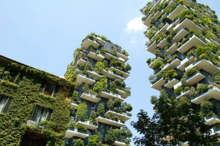 Two tall buildings with large green bushes and trees on their terraces.