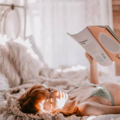 Woman lying on her bed with the sun on her face looking at a magazine.