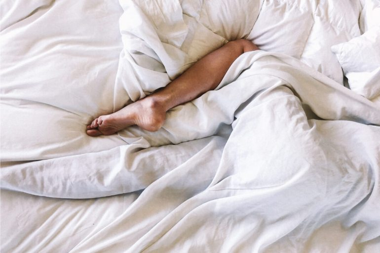 Woman lying in white bed sheets with leg poking out.