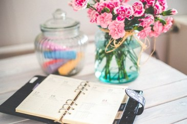 planner on a desk with flowers in a vase. A planner helps you in looking back and ahead.