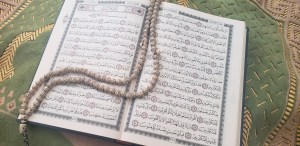 Muslim prayer beads on open Quran over prayer mat. One of Grandma's lessons was that she lived by prayer