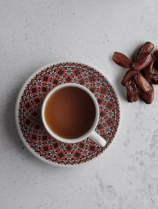 A cup of black coffee with some dates to the right side