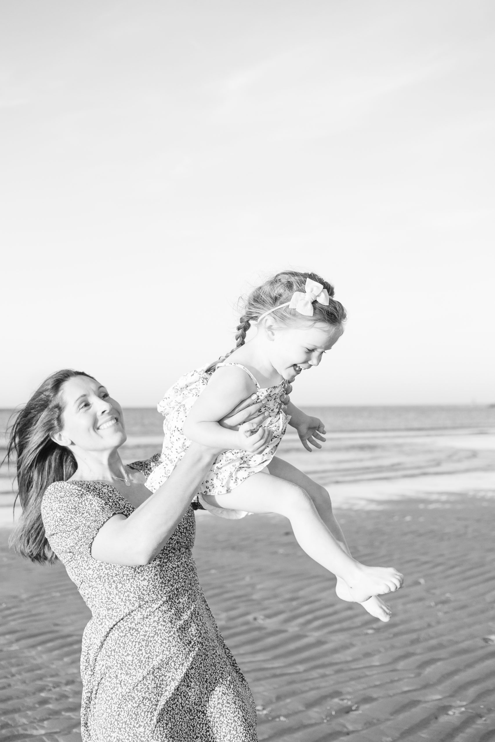 mother swinging daughter in the air at the beach during motherhood session